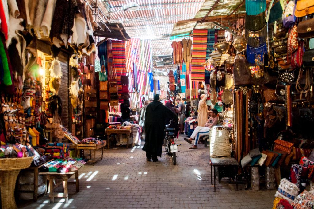 Bancarelle nell'ombreggiato suq di Marrakech, un uomo completamente coperto da una tunica passeggia tra schiere di bancarelle